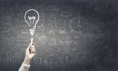 Photo pour Human hand darwing light bulb as idea concept with chalk - image libre de droit