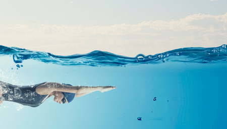 Photo pour Young woman swimmer in cap and glasses under water - image libre de droit