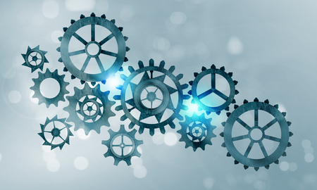 Mechanism of metal gears and cogwheels on blue background
