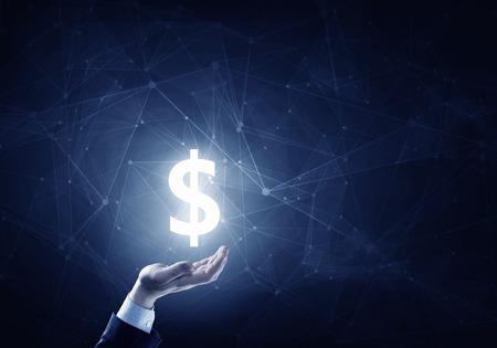 Foto de Businessman hands on dark background holding glowing dollar sign - Imagen libre de derechos