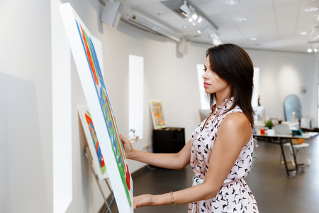 Photo pour Young caucasian woman standing in an art gallery in front of painting displayed on white wall - image libre de droit