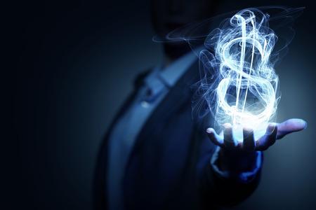 Photo pour Burning dollar sign in businesswoman palm on dark background - image libre de droit