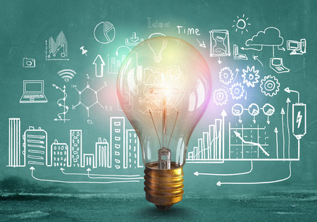 Foto de Glass glowing light bulb and business sketched ideas - Imagen libre de derechos