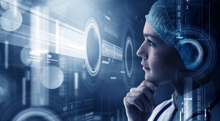 Photo pour Young woman scientist looking at virtual media screen - image libre de droit