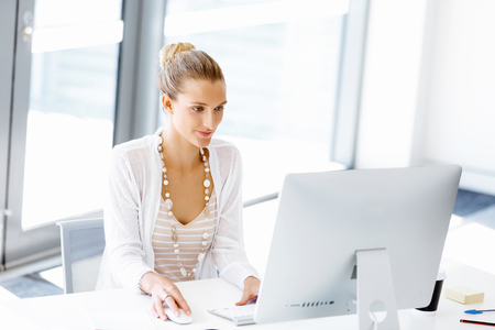 Photo pour Attractive woman sitting at desk in office - image libre de droit