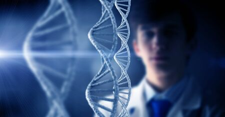 Young thoughtful male doctor looking at DNA molecule image