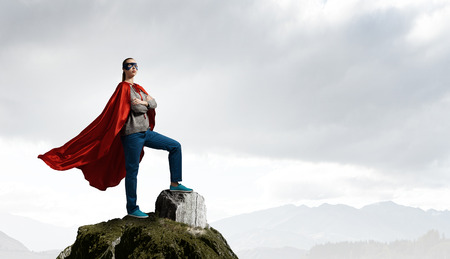 Photo for Young confident woman in red cape and mask on rock top - Royalty Free Image