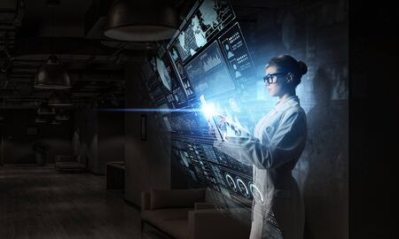 Young woman scientist using tablet pc in her hands. Mixed media