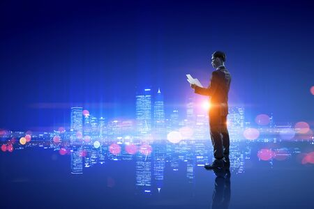 Photo pour Young businessman with papers in hands against night city background - image libre de droit