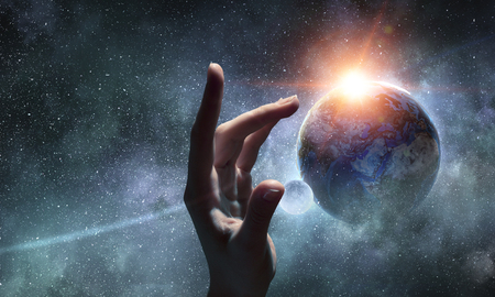 Photo for Female hand touching Earth symbolizing faith and religion. Elements of this iamge are furnished by NASA - Royalty Free Image