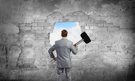 Photo for Businessman with hammer and hole in stone wall. Mixed media - Royalty Free Image