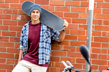 Foto de Teenage boy with skateboard standing next to the wall - Imagen libre de derechos