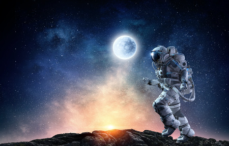 Photo for Astronaut in space suit running on planet surface. Mixed media - Royalty Free Image