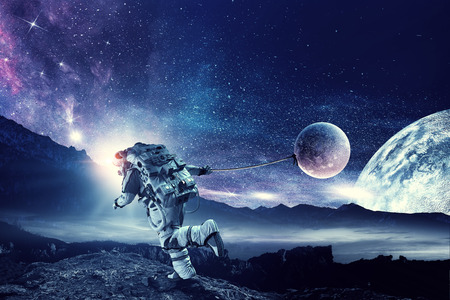 Photo pour Astronaut in outer space pulling planet on rope. - image libre de droit