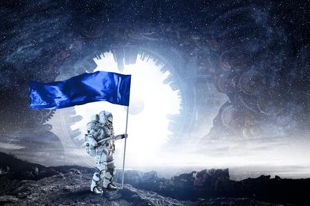 Photo pour Astronaut man with flag in hand. Mixed media - image libre de droit