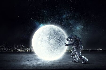 Photo for Astronaut in suit making planet roll. Mixed media - Royalty Free Image
