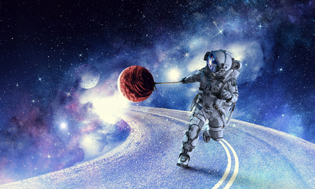 Photo for Astronaut in outer space pulling planet on rope. - Royalty Free Image