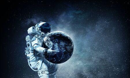 Photo pour Astronaut carrying Earth planet in hands. - image libre de droit