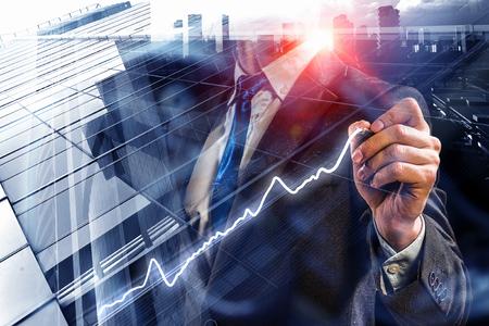 Foto de Close view of businessman drawing on screen market infographs - Imagen libre de derechos