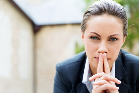 Photo for Portrait of young business woman outdoors sitting and thinking - Royalty Free Image