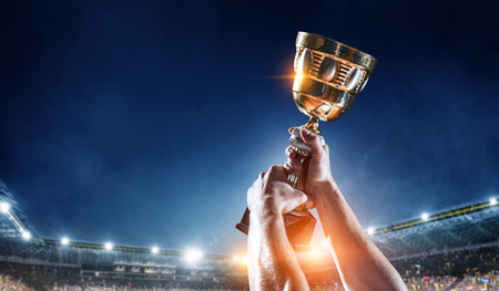 Photo pour Hand of athlete holding cup trophy against stadium. Mixed media - image libre de droit