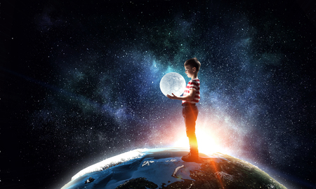 Photo for Boy holds the moon . Mixed media - Royalty Free Image