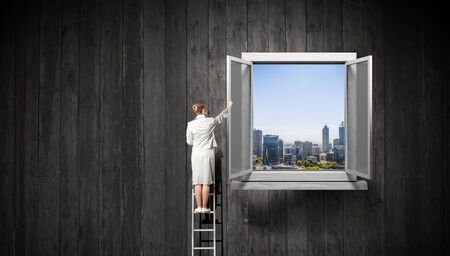 Photo pour Businesswoman standing on ladder and reaching up opened window in wall. Mixed media - image libre de droit