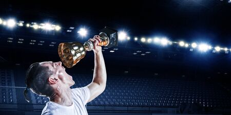 Photo for Soccer player drinking from his champion cup. Mixed media - Royalty Free Image
