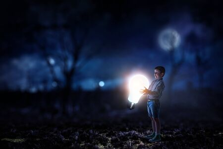 Photo for Boy holding a light bulb - Royalty Free Image