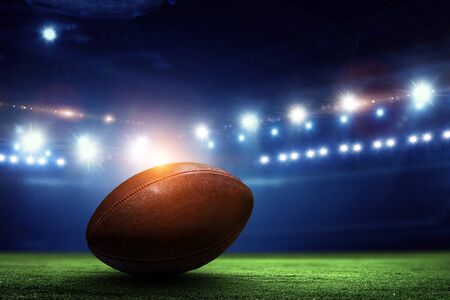 Photo pour Night football arena in lights and flashes with american football ball on the foreground - image libre de droit