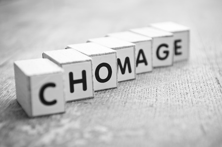Photo for concept word forming with cube on wooden desk background - Chomage unemployment,in french - Royalty Free Image
