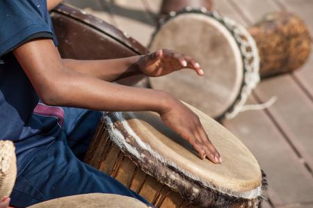 Closeup of kid's hands on African drums in outdoor