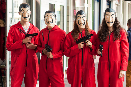 Mulhouse -  France - August 17 2018 :group of fans of the serie tv La casa de papel (paper house)  on Netflix standing in the street with costume and Salvador Dali mask and false shot guns