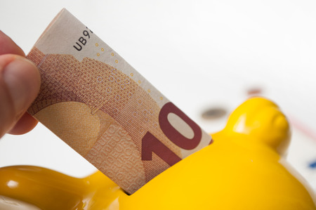 closeup of  hand of man putting ten euros bank note in yellow piggy bank on white background