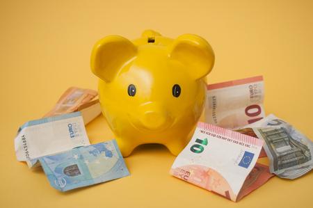 closeup of euros bank notes around a yellow piggy bank on yellow background