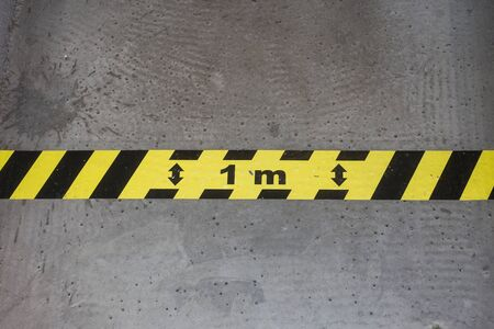 Photo pour Closeup of yellow and black stripped line on the floor - Social distancing line - image libre de droit