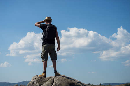 Photo pour Portait of man with backpack standing on the rocks at the top of the mountain on blue cloudy sky background - image libre de droit