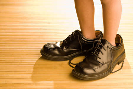 Photo for Big shoes to fill, child's feet in large grown-up black shoes, on backlit wood floor, playing dress-up - Royalty Free Image