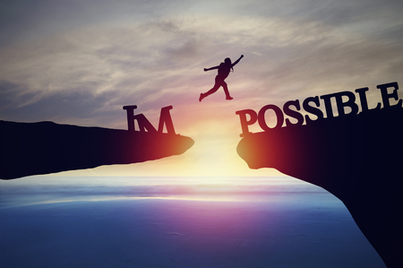 Foto de Silhouette of people jumping from cliff to other bank, concept as possible and impossible of success in business and leadership - Imagen libre de derechos