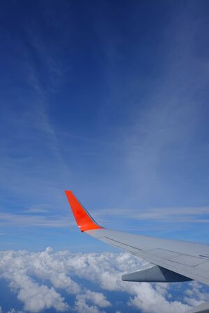 Photo for Wing of airplane with beautiful blue sky and clouds from airplane window, traveling  to oversea - Royalty Free Image