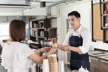 Photo pour Smiling Asian barista man holding cup of ice beverage to show the  customers in the coffee shop - image libre de droit