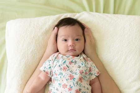 Photo pour Top view of a cute Asian baby girl wrapped up in bed - image libre de droit