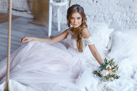 Foto de A bride with hairstyle and make up in gorgeous pink wedding dress and a vail with a bouquet of peonies. - Imagen libre de derechos