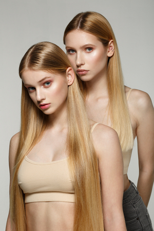 Photo pour Two sexy attractive twins woman with blonde long hair posing in glamour makeup - image libre de droit