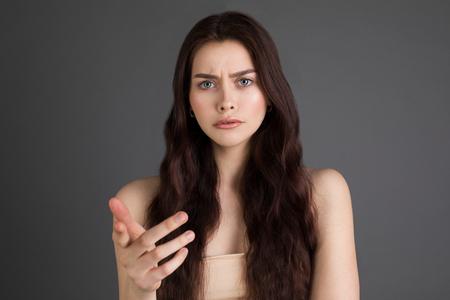Photo pour Portrait of an upset, serious, angry woman with long brunette hair - image libre de droit