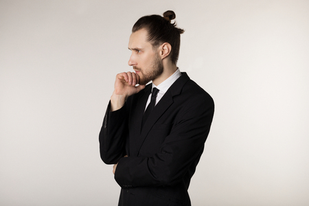 Photo pour Side view portrait of attractive young businessman in black suit with stylish hairstyle holding hand on chin with thoughtful expression - image libre de droit