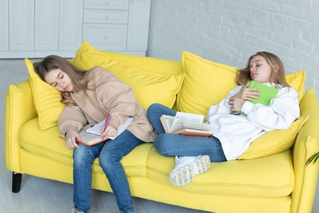 Foto de Two little sisters in casual clothes sleeping together on yellow sofa - Imagen libre de derechos