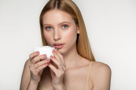 Photo pour Natural cosmetic. Taking good care of her skin. Attractive young woman looking at camera and smiling while standing against background - image libre de droit