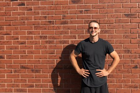 Photo pour Happy attractive young man in sunglasses, dressed in black t-shirt standing with hands on a belt, red brick wall on the background - image libre de droit
