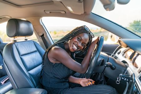 Photo pour Happy smiling african girl in black striped clothes is driving a car - image libre de droit